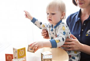 Child playing with toy building blocks, being held by his mom